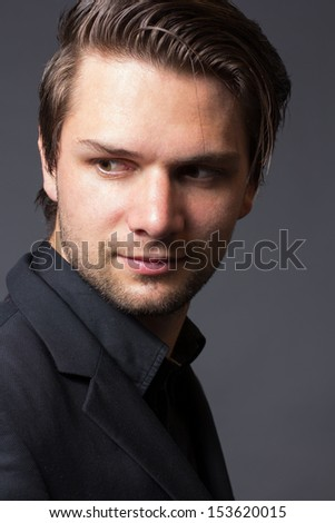 Face of a man in a Black Suit in front of a grey background looking serious - stock photo