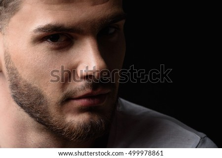 face of a man looking into the camera from darkness