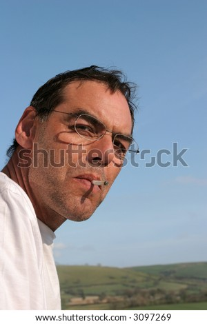 Face of a middle aged man wearing glasses and smoking a rolled up cigarette. Blue sky and countryside, out of focus, to the rear.