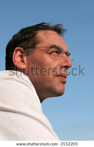 Face of a middle aged man wearing glasses looking thoughtful, set against a blue sky.