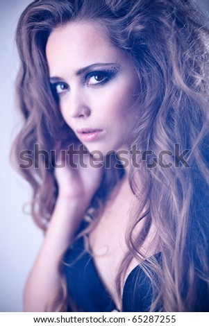 Face of a sexy young woman with creative makeup and long curly hair