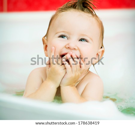 face of a smiling little baby in the bathroom - stock photo