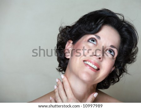 Face of a smiling woman with black curly hair, in her mid 30s with natural make-up and realistic skin texture with small fine lines