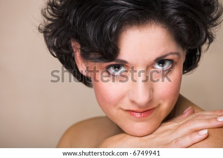 Face of a smiling woman with black curly hair, in her mid 30s with natural make-up and realistic skin texture with small freckles and fine lines