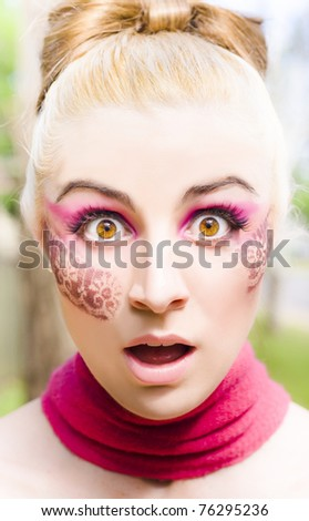 Face Of A Surprised And Shocked Blonde Woman Wearing Pink Scarf And Art Design Makeup, Within A Nature Background With A Look Of Surprise And Shock Horror - stock photo