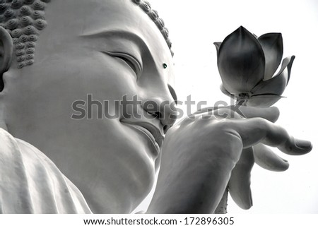 face of a white Buddha with a lotus in his hand, Dalat, Vietnam - stock photo