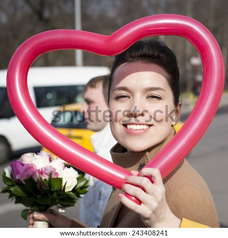 Face of a young adorable woman framed in the heart-shaped balloon on Valentine's Day - stock photo