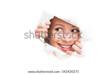 face of a young curious woman peeking through a  hole torn in white paper poster - stock photo