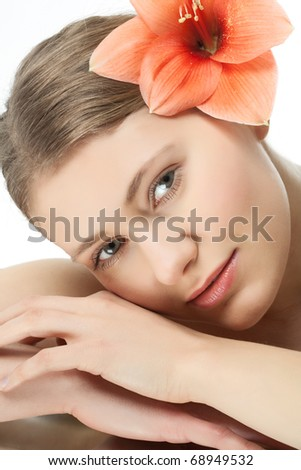 Face of a young woman with a flower - stock photo