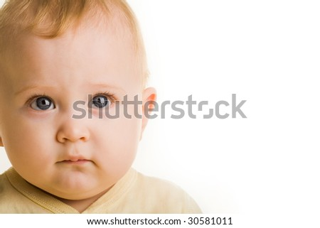 Face of adorable baby looking at camera seriously over white background - stock photo