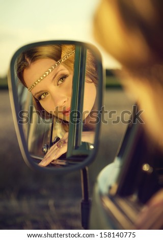 face of an attractive brunette woman in the rear mirror of an old car - stock photo