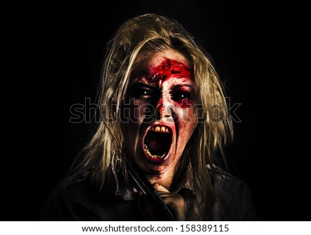 Face of an evil zombie girl screaming out in bloody horror while holding a hand saw on black background - stock photo