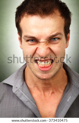 Face of angry furious young man - stock photo