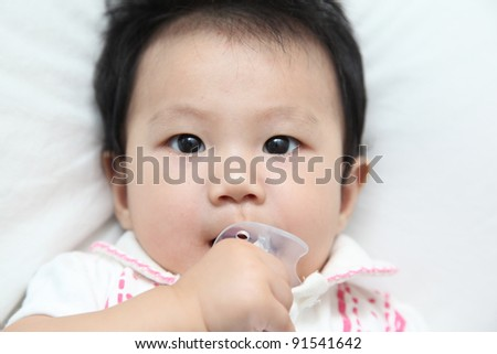 Face of asian baby about 6 months and child's pacifier in her mouth - stock photo