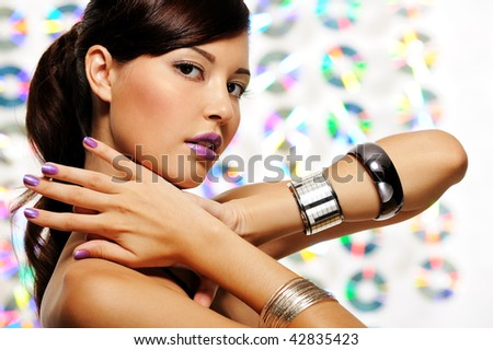Face of attractive young woman with purple fingernails and lipstick - stock photo