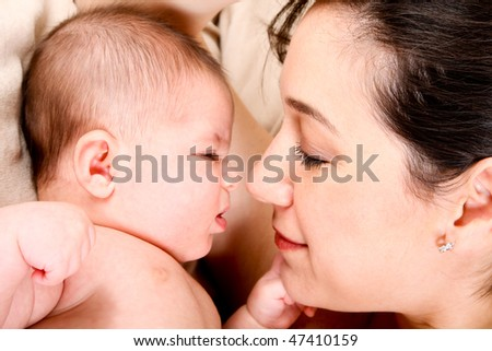 Face of baby and mother together, infant expressing anger and holding fist ready to punch.