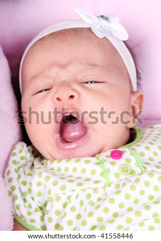 Face of beautiful baby yawning on a pink blanket - stock photo