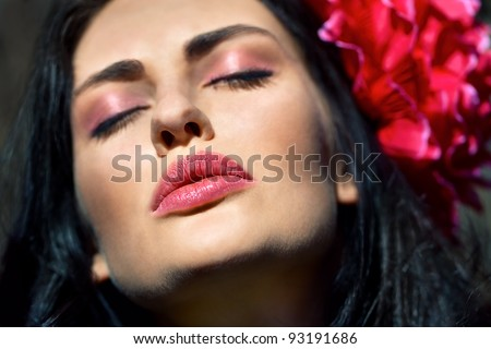 Face of beautiful girl with a flower in her hair - stock photo