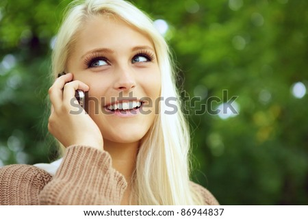 Face of beautiful happy young blonde girl using a cellphone and smiling with green foliage behind.