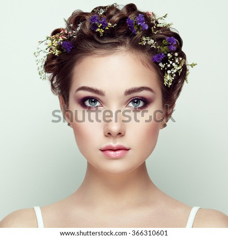 Face of beautiful woman decorated with flowers. Perfect makeup. Beauty fashion. Eyelashes. Cosmetic Eyeshadow - stock photo