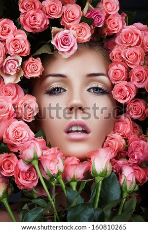 Face of beautiful woman in a bouquet of red roses - stock photo