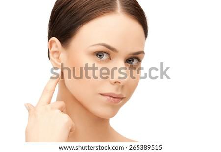 face of beautiful woman touching her ear - stock photo