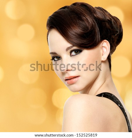 Face of beautiful woman with fashion hairstyle and glamour makeup - over creative soft bokeh background - stock photo