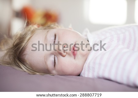 face of blonde caucasian baby nineteen month age with pink and white stripped jersey sleeping on brown sheets king bed
