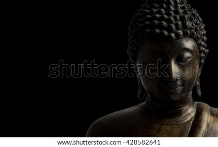 face of brass Buddha statue, low key light, black isolated background, copy space on left side.