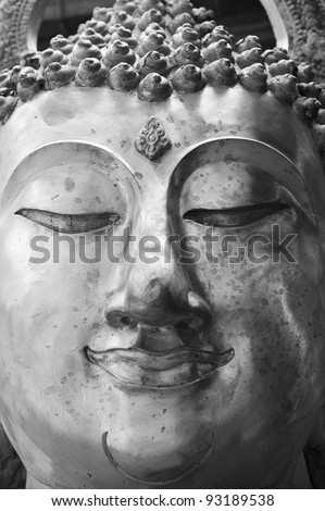 Face of Buddha statue in black and white - stock photo