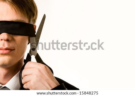 Face of businessman wearing black band on his eyes and holding scissors trying to cut it - stock photo