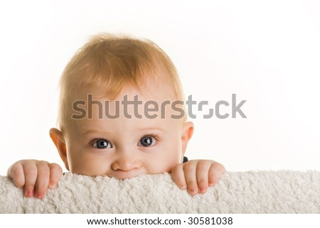 Face of curious baby peeping out of board over white background - stock photo
