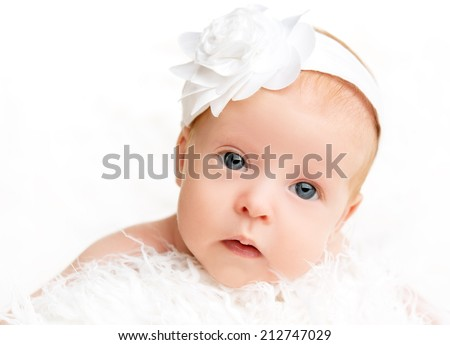 face of cute  newborn baby girl with a pink flower ribbon - stock photo
