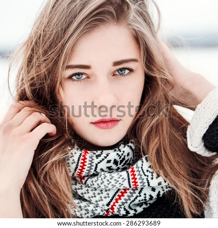 face of cute young girl on winter background - stock photo