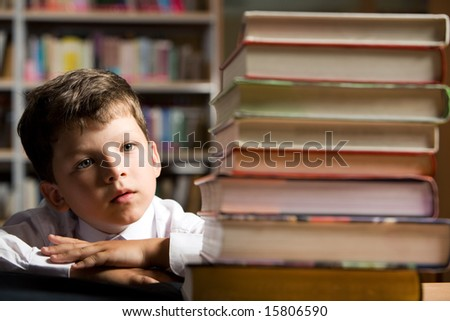 Face of diligent schoolboy looking at stack of books in the library