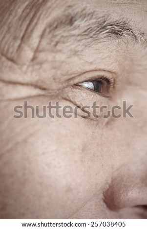 Face of elderly man looking away. Vertical photo - stock photo