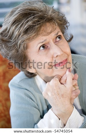 Face of elderly woman looking up with serious expression - stock photo