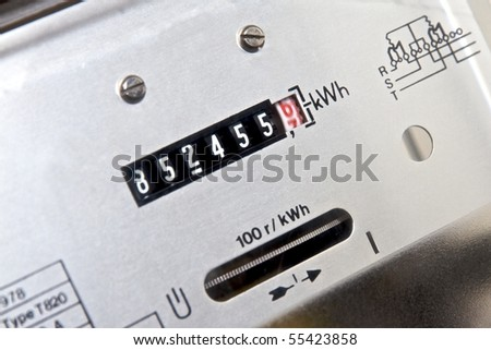 Face of electromechanical induction meter in household circuit breaker cabinet. Horizontal aluminum rotor disc. Selective focus on motion blurred red dial. - stock photo