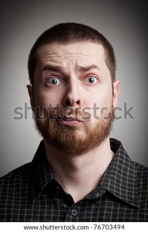 Face of funny amazed guy isolated on gray background - stock photo