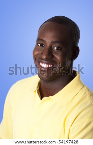 Face of handsome happy African American corporate business man smiling, wearing yellow polo shirt on a blue sky-like background. - stock photo