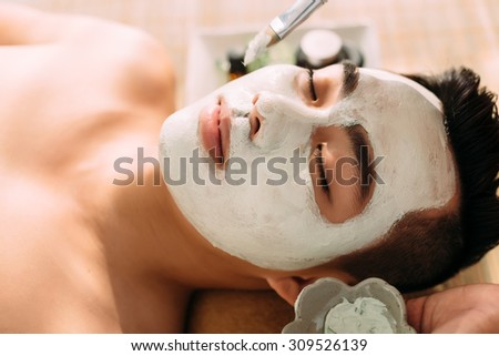 Face of handsome man having spa treatment in beauty salon - stock photo