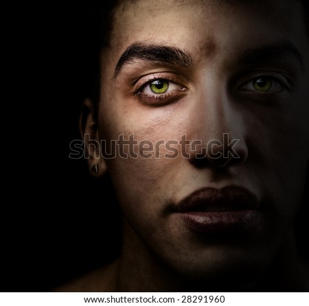 Face of handsome man with green eyes in the shadow - stock photo