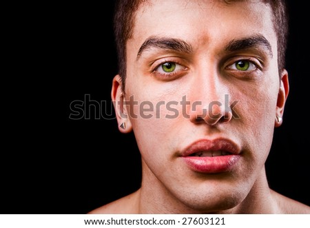 Face of handsome sensual man isolated on black background - stock photo