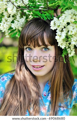 face of happy pretty girl standing under blossom of acacia - stock photo