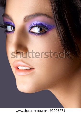 face of Italian beautiful woman with purple eyeshadows and soft smile.. - stock photo