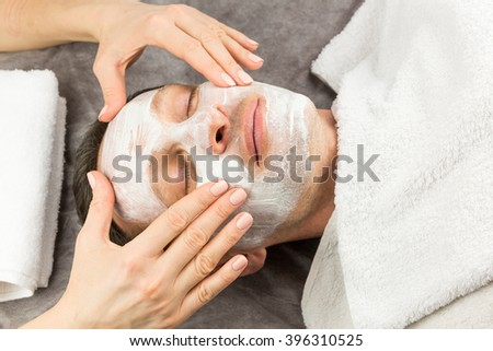 Face of laying man with cream mask and hands of beautician, beauty, spa - stock photo