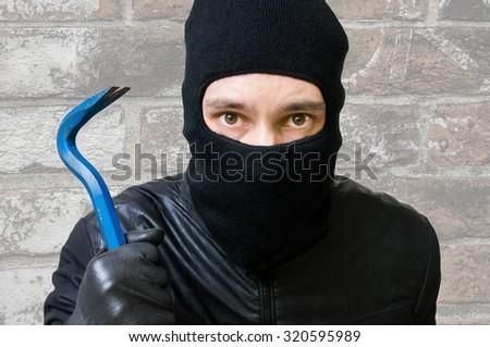 Face of masked criminal burglar with balaclava that holds crowbar - stock photo