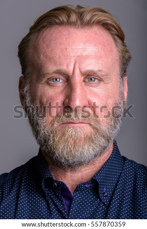 Face of mature bearded man in gray background