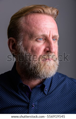 Face of mature bearded man thinking in gray background