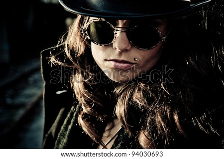 Face of mystery brunette woman wearing dark glasses and a hat, dark closeup outdoor portrait. - stock photo